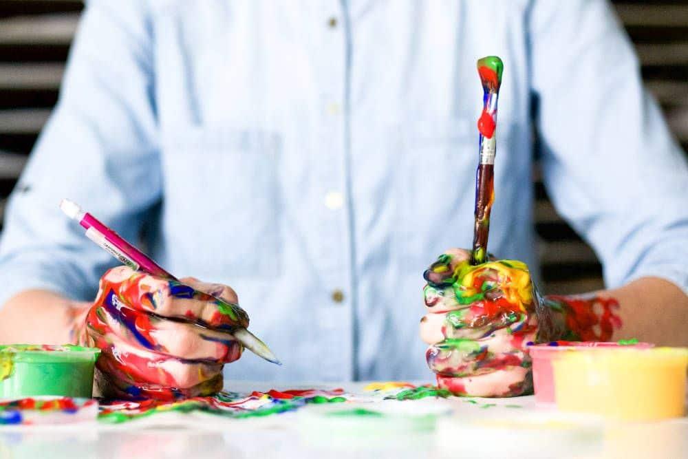 człowiek z rękoma poplamionymi farbą